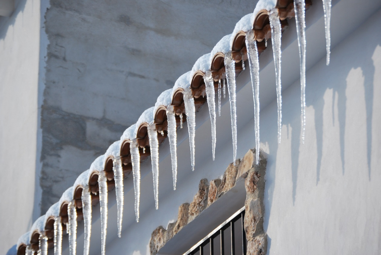 Icicles hanging from the eaves of a roof.